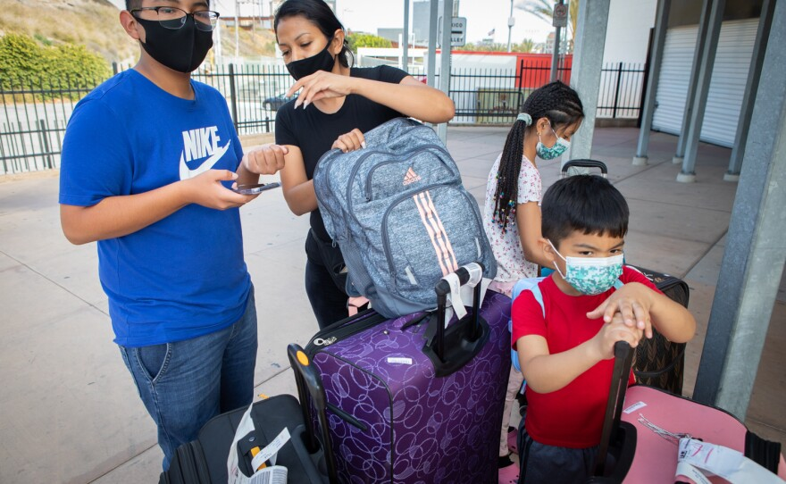 Michelle Arenas waits with her three children for a shuttle bus to Las Vegas at the San Ysidro Transit Center, June 6, 2020. The family began their day of travel in Michoacán, where they were attending a wedding.