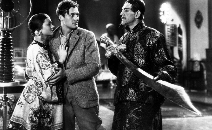 """Terrence (Charles Starrett) falls into the clutches of Fu Manchu (Boris Karloff) and his daughter Fah Lo See (Myrna Loy) in the 1932 pre-Code Hollywood film """"The Mask of Fu Manchu."""""""