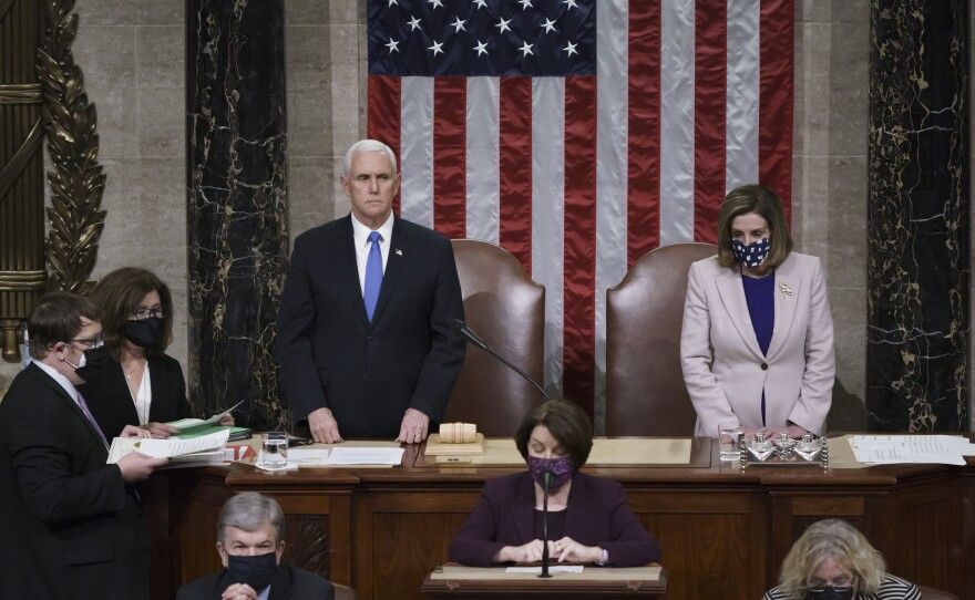 Vice President Mike Pence and Speaker of the House Nancy Pelosi, D-Calif., read the final certification of Electoral College votes cast in November's presidential election during a joint session of Congress after working through the night, at the Capitol in Washington, Thursday, Jan. 7, 2021.