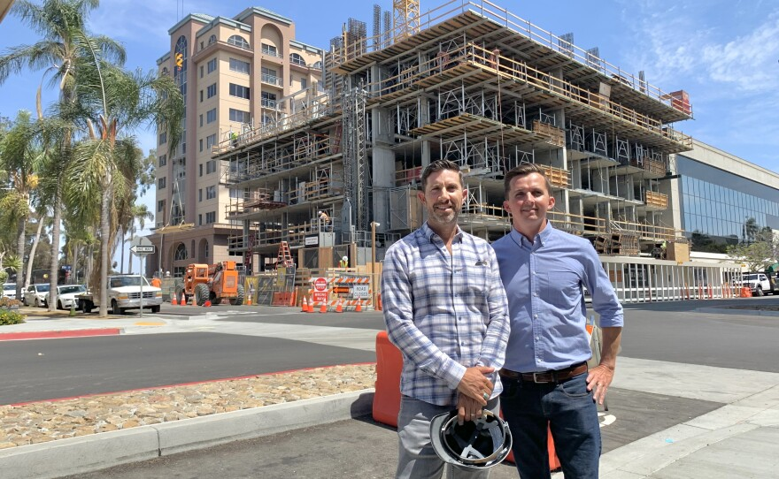 Gilman Bishop, left, and Ryan Wynn stand in front of their 100-unit apartment building under construction in Bankers Hill, June 15, 2021.