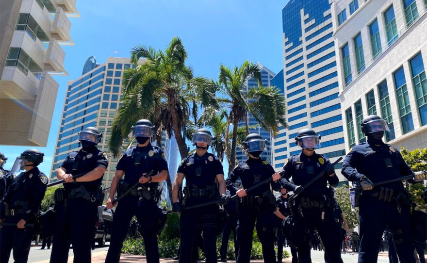 A line of police officers observe protesters during a demonstration in downtown San Diego, May 31, 2020.
