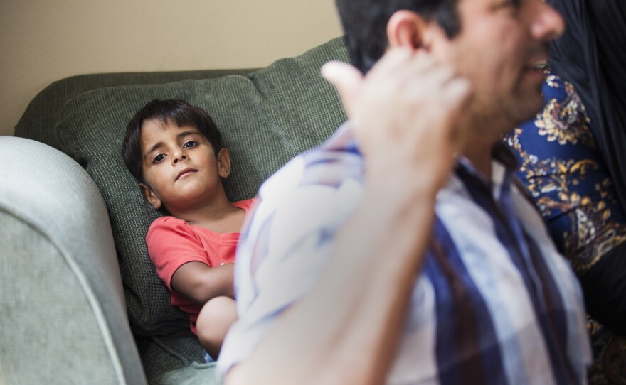 The youngest member of the Hamdard family leans back on the family's couch while his father, Lalmir, is seen in the foreground, Aug. 1, 2017.
