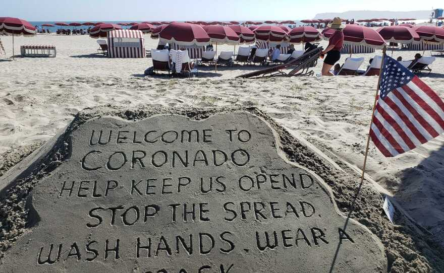 Sand art at the Hotel del Coronado on July 12, 2020, asking visitors to wear a mask as an employee sets up beach chairs in the background.
