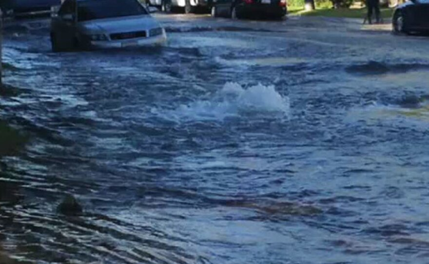 A car is surrounded by water after a water main ruptured in a Birdland-area neighborhood, Sept. 3, 2014.