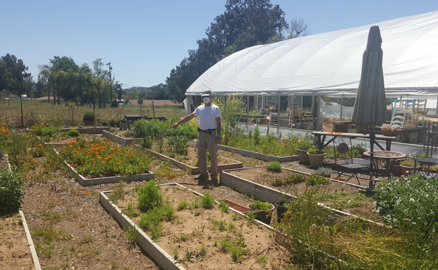 Joe Zenovic of San Diego Organic Farms in Ramona stands next to a greenhouse where the farm propagates plants from seed, April 22, 2020.