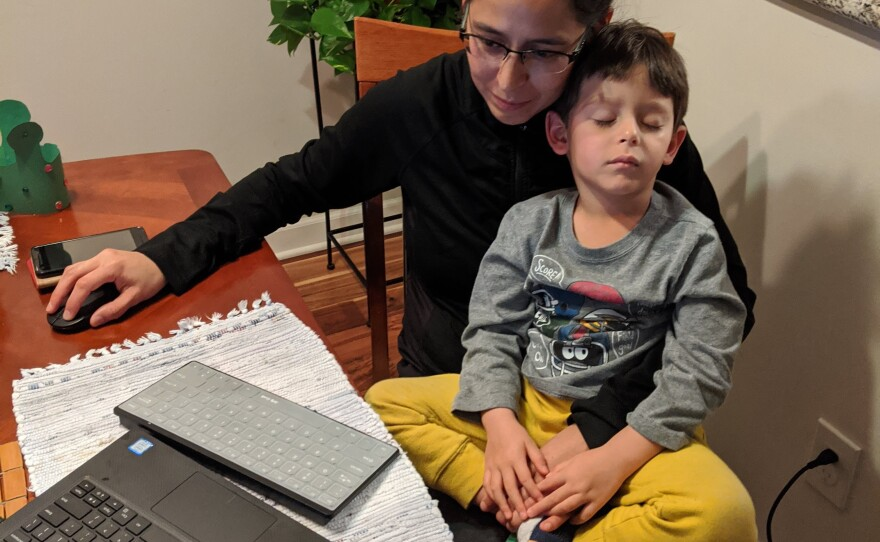 Julia Najera attempts to work from home with her son in her lap in this undated photo.