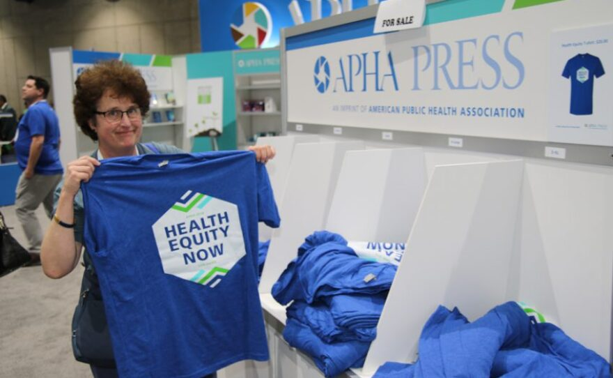 """An attendee at the 2018 American Public Health Association conference in San Diego holds up a T-shirt that says """"Health Equity Now,"""" Nov. 12, 2018."""