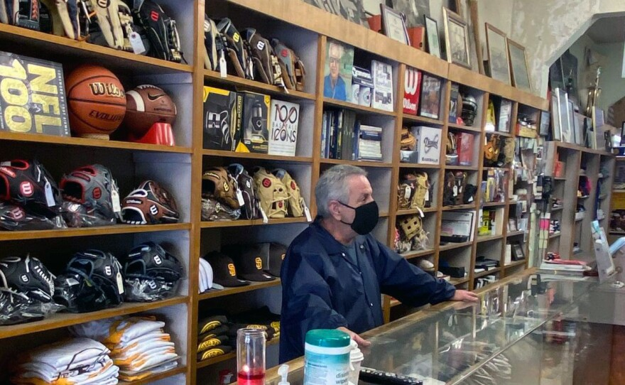 Gregg Schloss stands behind the counter on the last day A&B Sporting Goods in North Park was open, Jan. 2021.