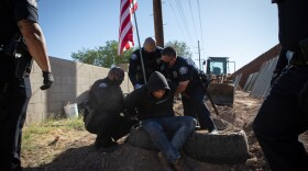 Calexico police officers arrest Hugo Castro who refused to move from the community garden at the Calexico farmworkers encampment, April 7, 2020. Castro is one of the organizers who started the encampment in January.