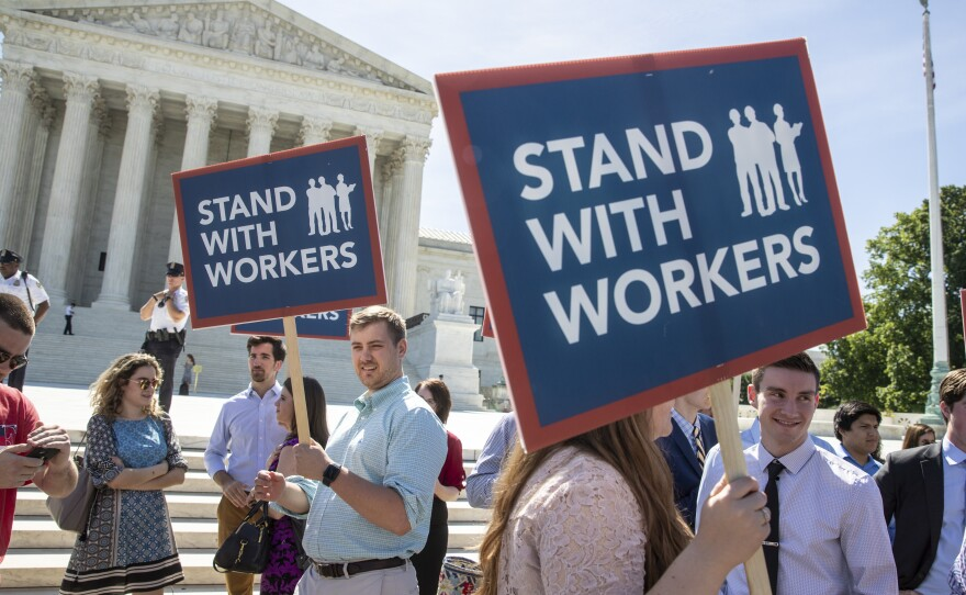 People gather at the Supreme Court awaiting a decision in an Illinois union dues case, Janus v. AFSCME, on Monday.