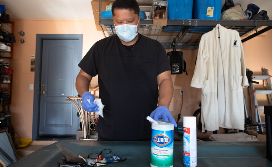 Nurse George Santiago sanitizes his personal belongings after returning home from a hospital shift at Palomar Medical Center Escondido, March 3, 2021.