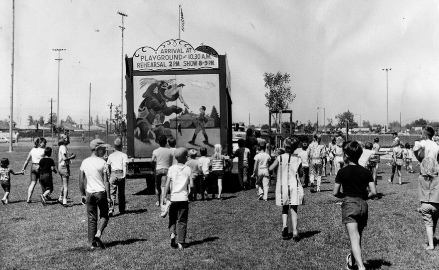 Children follow a truck as it drives into position at Granada Hills Playground to set up the 1964 Combined Traveling Circus and Kiddie Carnival, July 4, 1964.