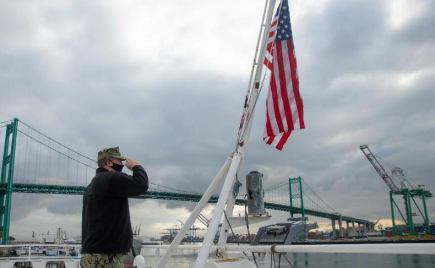 Sailor John Arkulary from Marshfield, Wis. salutes the flag aboard the hospital ship USNS Mercy in Los Angeles, April 13, 2020.