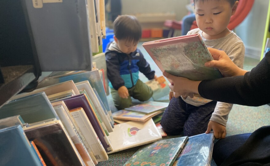 Four-year-old Patrick Jang looks down at a picture book that his mother is holding while he sits among stacks with his brother in the children's section at the San Diego Central Library, Dec. 30, 2019.