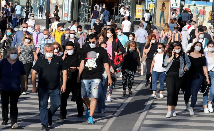 Face masks definitely help keep the coronavirus at bay — and are embraced by most people in this scene from Ankara. But what about earlier recommendations to keep 6 feet from others and limit close contact to 15 minutes. With the highly contagious delta variant, are these still effective protective measures?