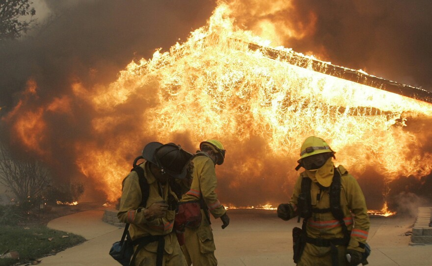 Three firefighters brace themselves from explosive heat coming from a burning home in the Rancho Bernardo area of San Diego, set off by a wildfire seen here in a file photo taken Monday, Oct. 22, 2007.