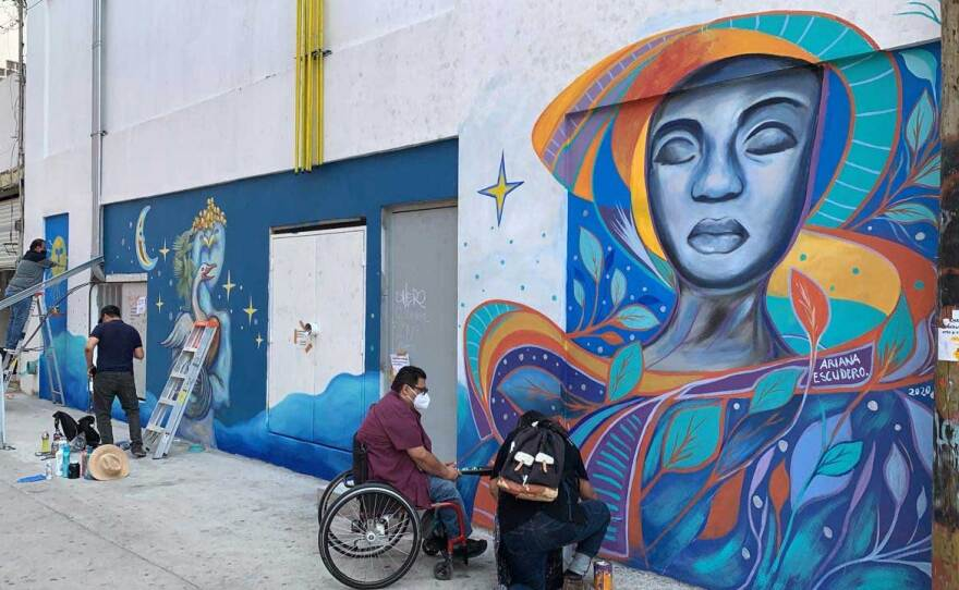 """Artists work on Ariana Escudero's mural in Tijuana on September 11, 2020 for the """"Walls/Muros"""" cross-border project."""