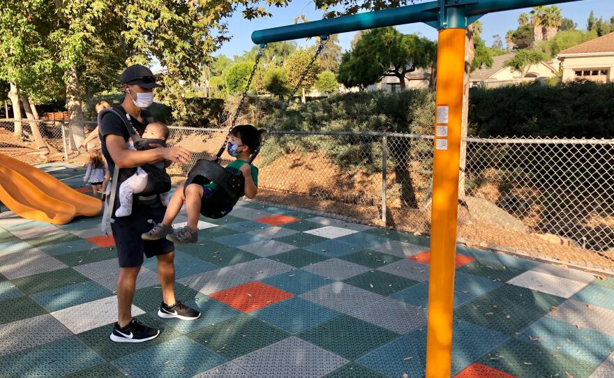 A family plays in a public playground in Poway, Oct. 2, 2020.
