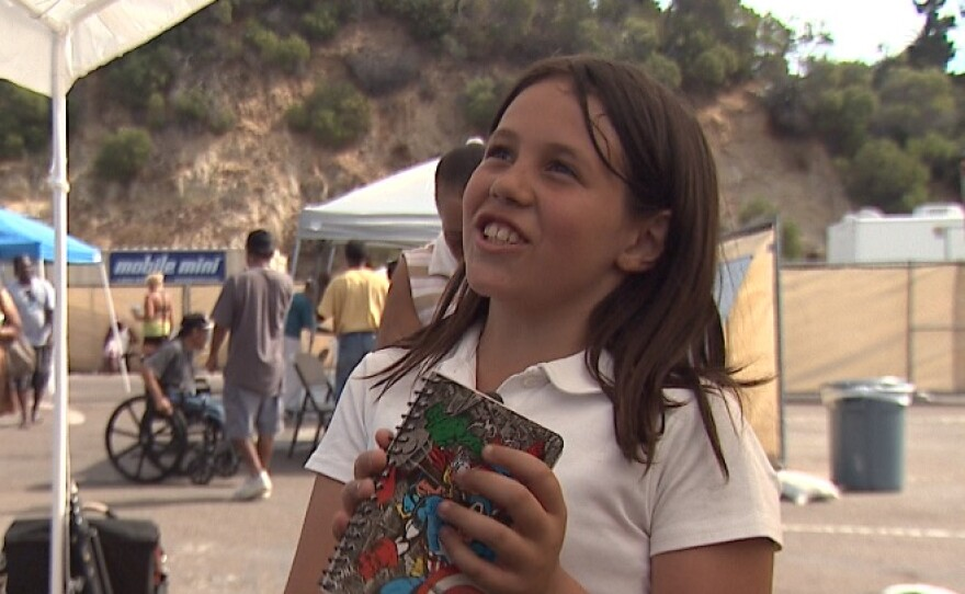 Azaura Anjos, 10, holds her journal that she uses to write about people she has met at the homeless transitional camp, Oct. 17, 2017.