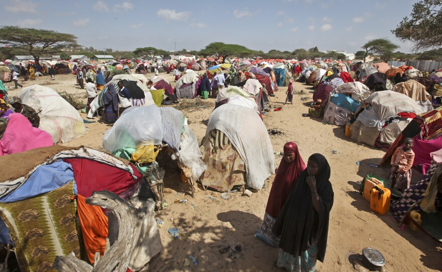 Newly displaced Somalis walk through a camp in the Garasbaley area on the outskirts of Mogadishu, Somalia, Tuesday, March 28, 2017.
