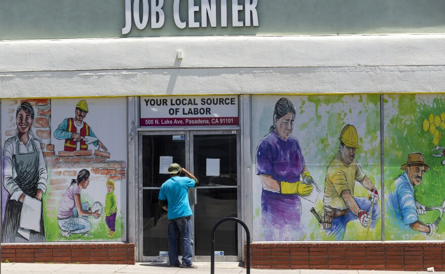 A person looks inside the closed doors of the Pasadena Community Job Center during the coronavirus pandemic in Pasadena, Calif. May 7, 2020.