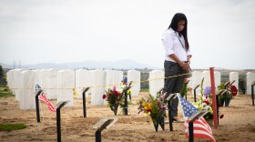 Witchelda Bondoc stands over her husband Joseph Bondoc's grave at Miramar National Cemetery on June 30, 2020. Bondoc died from COVID-19 in May.