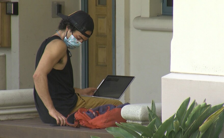 A student works on laptop outside on the campus of San Diego State, August 31, 2020.