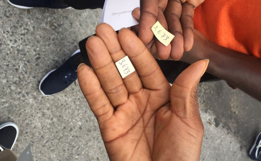 Two asylum-seekers from Cameroon hold out their numbers holding their spot on the unofficial list of asylum-seekers on July 16, 2019.