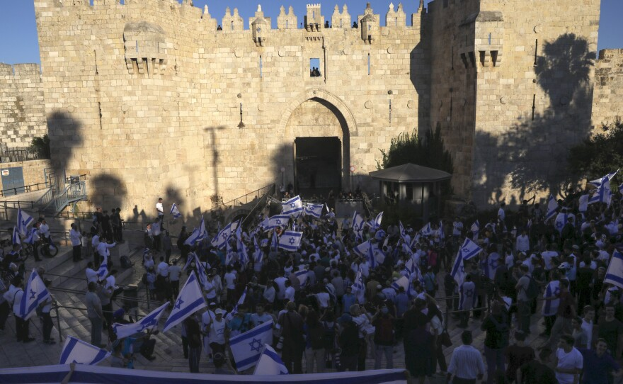 """Jewish ultranationalists wave Israeli flags participate in the """"Flags March"""" next to Damascus gate, outside Jerusalem's Old City, Tuesday."""