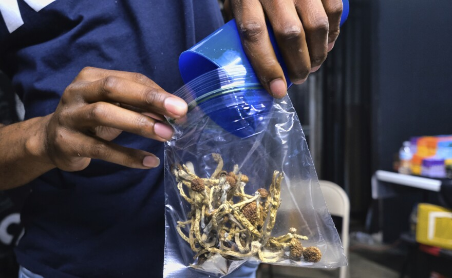 In this Friday, May 24, 2019 photo a vendor bags psilocybin mushrooms at a cannabis marketplace in Los Angeles.