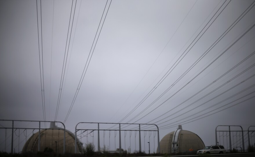 Power lines make their way over a freeway toward the San Onofre nuclear power plant, June 7, 2013.