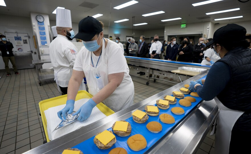 Workers prepare burgers for hundreds of migrants female teenagers set to arrive at the San Diego Convention Center Saturday night, March 27, 2021.