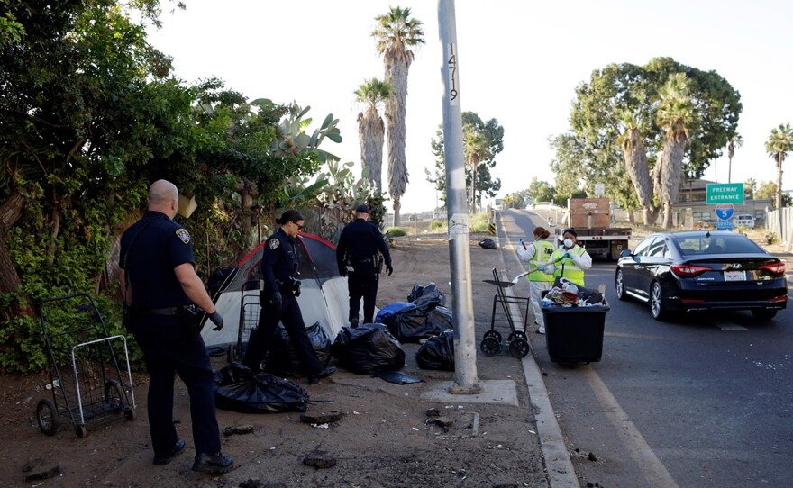 Police officers remove a tent left by the homeless during efforts to sanitize neighborhoods to control the spread of hepatitis A, in San Diego., Sept. 25, 2017.