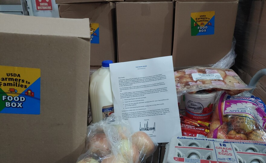 This undated photo shows food boxes that will head out to families in the San Diego Unified School District. Also shown is a letter from President Donald Trump, which will not be included in the boxes.