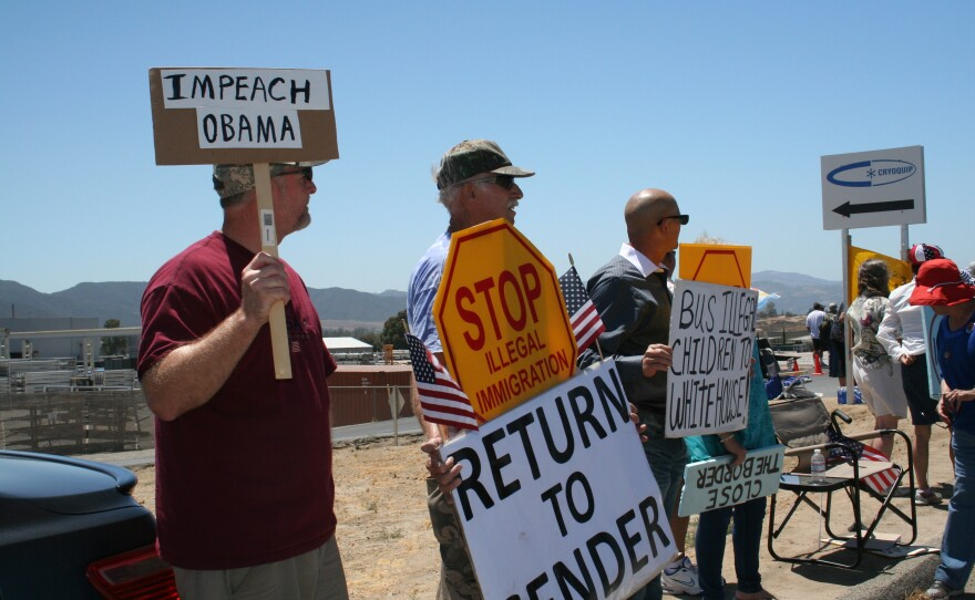 Protesters hold signs along a road in Murrieta, July 1, 2014.