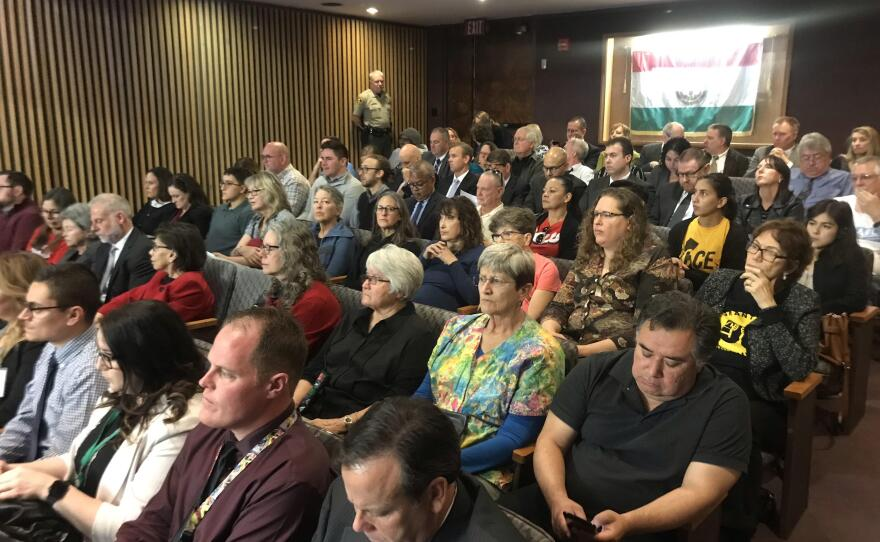Members of the Rapid Response Network and of the public watch a San Diego County Board of Supervisors meeting on housing asylum seekers, Jan. 29, 2019.
