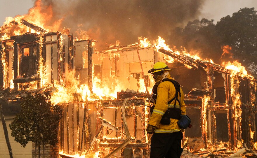 A firefighter monitors a house burning in Santa Rosa, Calif., Monday. Wildfires whipped by powerful winds swept through Northern California sending residents on a headlong flight to safety through smoke and flames as homes burned.