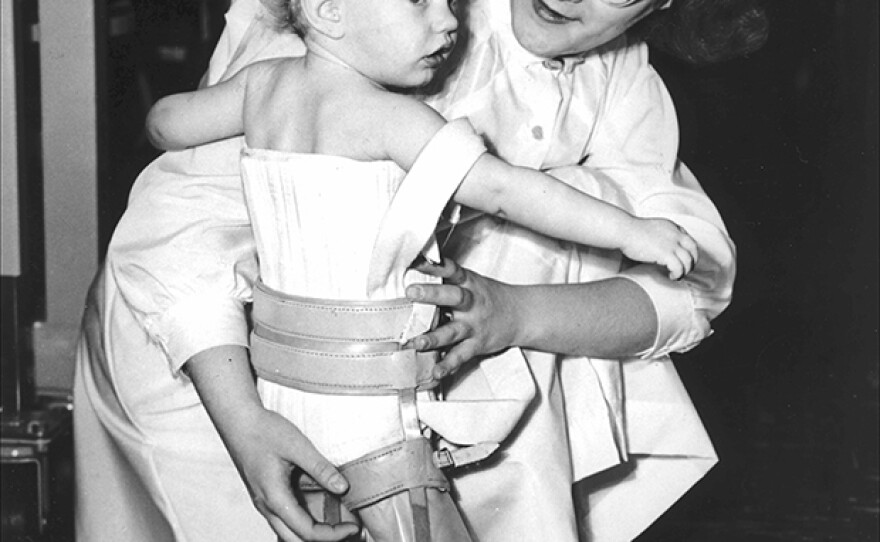 Nurse holds toddler, who is wearing leg and chest braces. (undated photo)