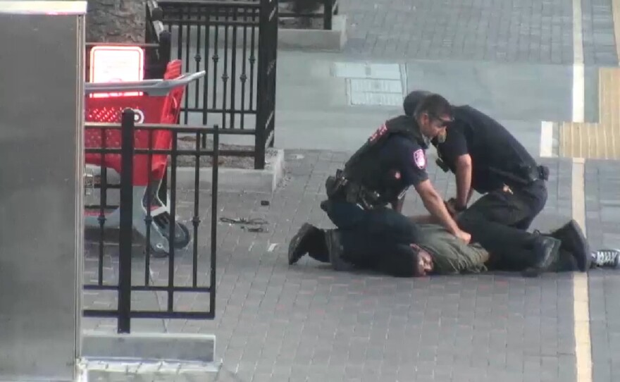 Angel Zapata Hernandez is pinned to the ground by a MTS code compliance officer and a private Transit System Security officer near the downtown Santa Fe Depot, Oct. 15, 2019.