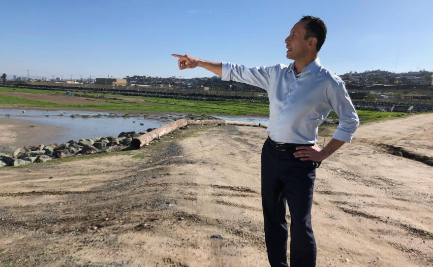 Rafael Castellanos, a candidate for San Diego County's first supervisorial district, points toward what he says is polluted water in the Tijuana River Valley, Jan. 22, 2020.