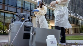 Researchers collecting data from an automated collection machine on the UC San Diego campus that captures sewage flows to track COVID-19 infections on Aug. 11, 2021.