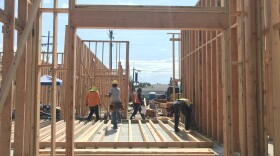 Construction workers set up the framing of an apartment building in North Park, July 23, 2019.