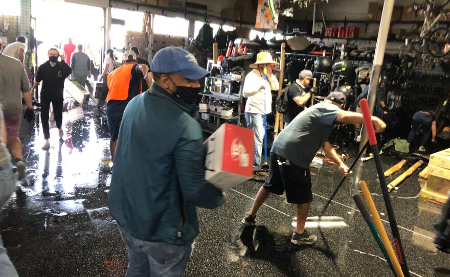 Community members clean up inside a vandalized Play It Again Sports in La Mesa and mop up water after a fire set during protests triggered an emergency sprinkle system, May 31, 2020.