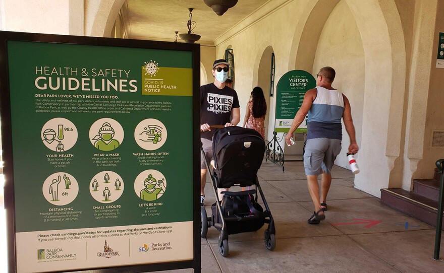 A man with a stroller on Aug. 1, 2020, walks by a Balboa Park health and safety guidelines sign design to help stop the spread of the coronavirus.