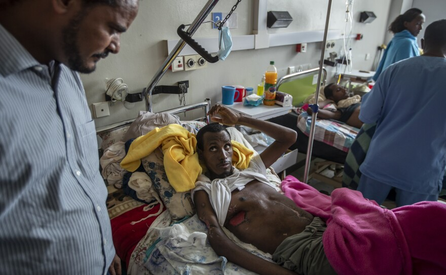 In a May 6, 2021 file photo, a farmer, Teklemariam Gebremichael, who said he was shot by Eritrean forces in Enticho six months before and is still recovering, speaks to a doctor, left, at the Ayder Referral Hospital in Mekele, in the Tigray region of northern Ethiopia. The United States on Monday imposed sanctions on Eritrea's chief of staff of the defense forces.
