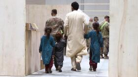 An Afghan family walks toward a medical screening station while in-processing at Camp Buehring, Kuwait. Aug. 23, 2021.