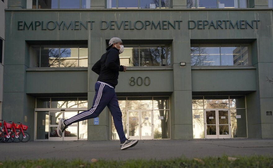 Above, a runner passes the office of California's Employment Development Department in Sacramento in December 2020.