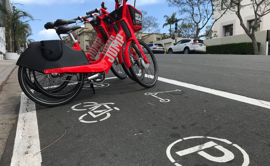 Electric bikes are seen parked in a newly painted dockless bike and scooter parking area downtown, April 19, 2019.