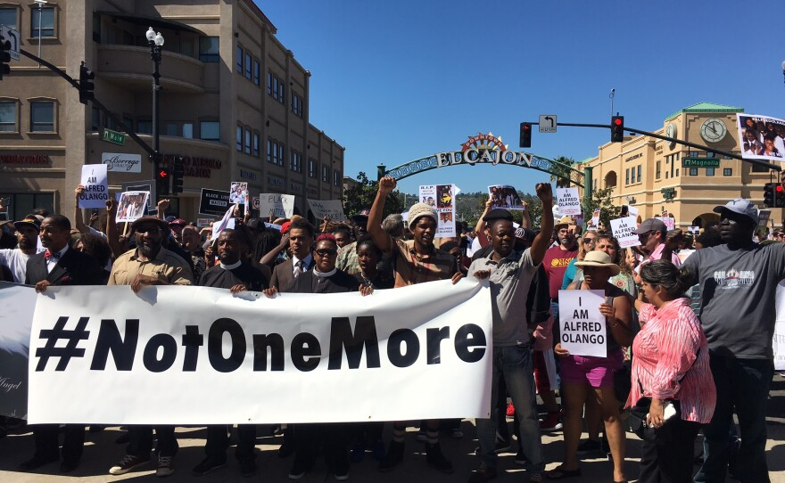 """A crowd of several hundred demonstrators march peacefully down Main Street in El Cajon, Oct. 1, 2016. They carry signs that read """"Not One More"""" and """"I Am Alfred Olango."""" Police officers fatally shot Olango, a Ugandan immigrant living in El Cajon, Sept. 27, 2016."""