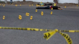 Investigators mark the spot where spent bullet casing fell next several bodies lying on a road in the town of Navolato, Sinaloa state, Mexico, June 29, 2017.
